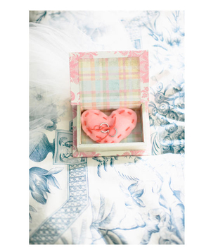 A small printed box holds a hand-sewn heart-shaped ring pillow