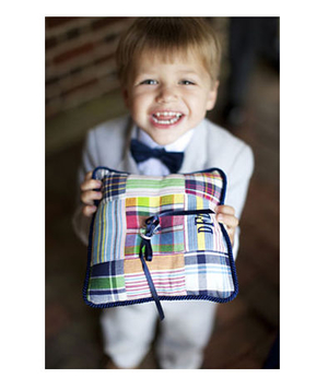 A boy holds a preppy plaid ring pillow