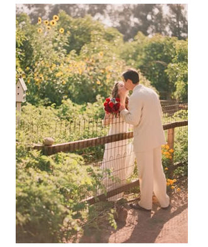 Bridge and groom kiss over fence in backyard