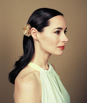 Woman with hair behind ear and floral barrette