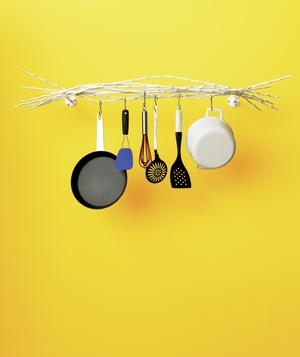 White branch-like hanging kitchen rack in front of yellow wall