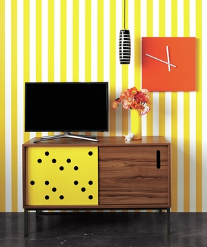 Console with yellow holes in front of yellow striped wall