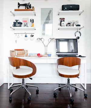 Long white desk on white wall with two chairs