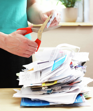 Woman cutting up credit card over a pile of receipts
