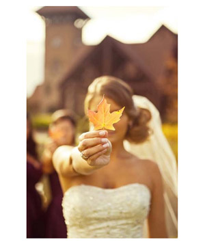 Bride holding maple leaf in front of her face
