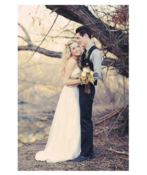 Wedding couple posing in front of leafless tree