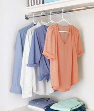 Drying bar with shirts hanging, shelf with folded clothes below