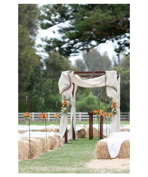 Outdoor wedding aisle lined with hay bales and flowers in mason jars
