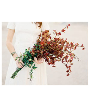 Arm bouquet of maroon and chocolate oncidium orchids and white passion vine