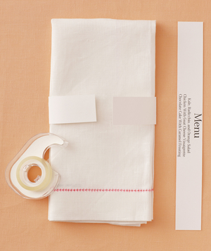 Cloth napkin with paper menu band, and roll of clear tape