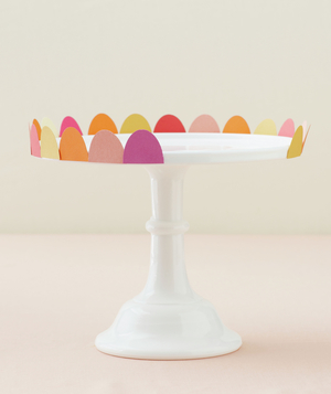 Cake stand being decorated by different-colored paper