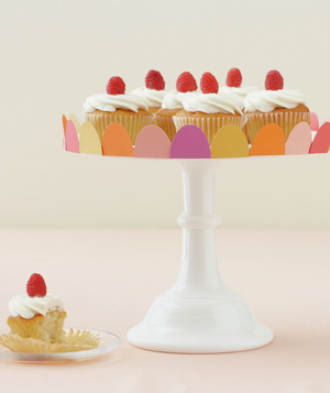 Decorated cake stand with raspberry-topped cupcakes
