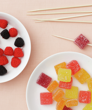 Candies on white plates and pile of toothpicks