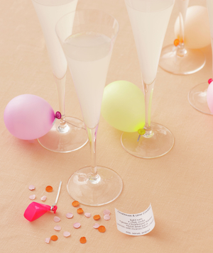 Champagne glasses with mini-balloons and confetti, printed drink recipe