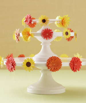 White cake stand decorated by orange and yellow floral stickers