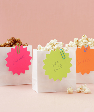 White bags of popcorn labeled caramel, kettle, and sea salt