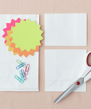 Scissors, white paper bags, colorful paper in shapes