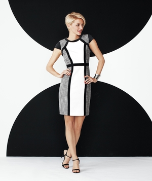 Model wearing black, white, and gray Calvin Klein dress with black heels