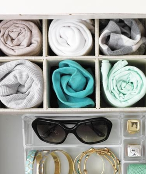 Drawer with dividers showing rolled up tees and accessories