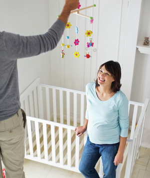 Couple decorating baby's room with colorful mobile