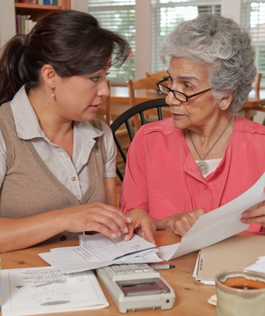 Adult woman helping senior mother with finances