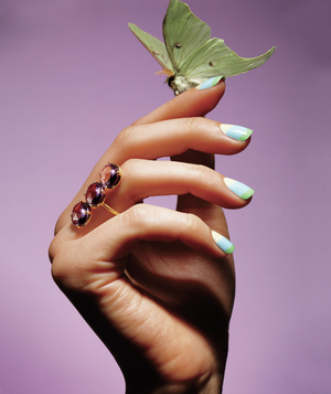 Luna moth perched on hand with amethyst ring and pastel-striped nails