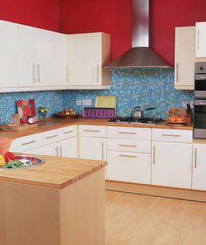 Kitchen with red walls, blue backsplash tiles and white cabinets