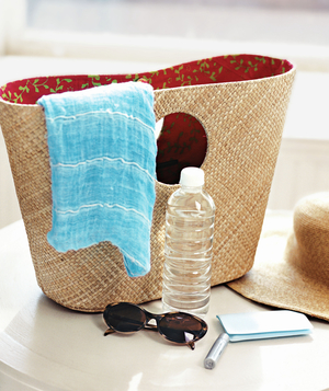 Basket with sunglasses, bottle of water, lip balm, straw hat, scarf