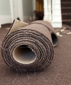 Brown carpet roll with stairs and carpet remnants in the background