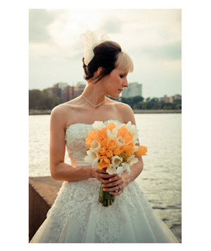 Bride with bouquet of orange and white tulips standing in front of water