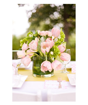 Wedding table vase with pink tulips and green leaves
