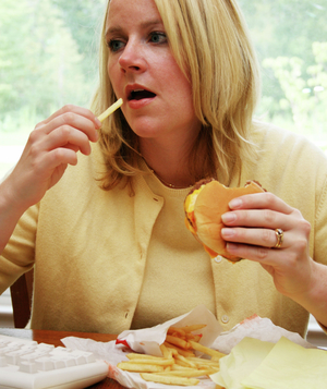 Woman eating hamburger and french fries at her desk