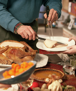 Man serving guests at Thanksgiving dinner