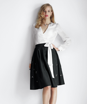 Model wearing white wrap top and black skirt