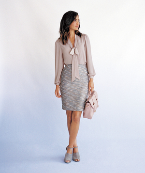 Model wearing bow blouse with tweed skirt