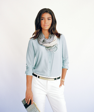 Model wearing light blue blouse with scarf and cream trousers