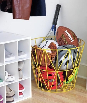 Basket with sports equipment next to shoe storage