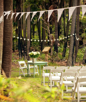 White chairs at outdoor wedding ceremony
