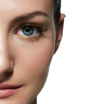 Half of model's face with gold lashes