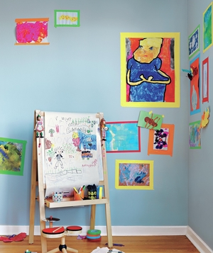 Kid's room with easel and many colorful paintings on the walls