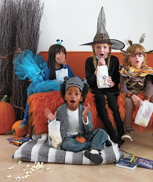 Kids in costumes watching scary movie at Halloween party