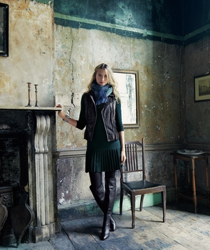 Model wearing dress, leather vest, blue scarf and over-the-knee boots