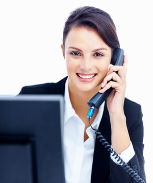 Smiling woman on phone in front of computer