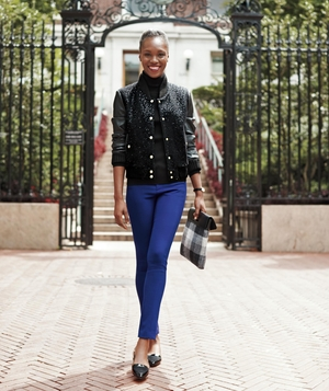 Model wearing blue pants and black varsity-style jacket