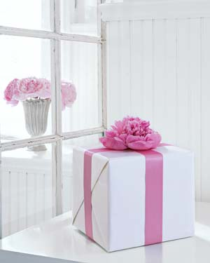 A gorgeous fresh flower attached with double-sided tape and a satin ribbon adds a feminine touch.