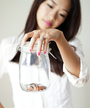 Woman holding almost empty coin jar