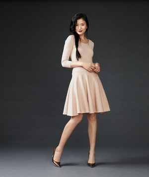Model in peach flared dress