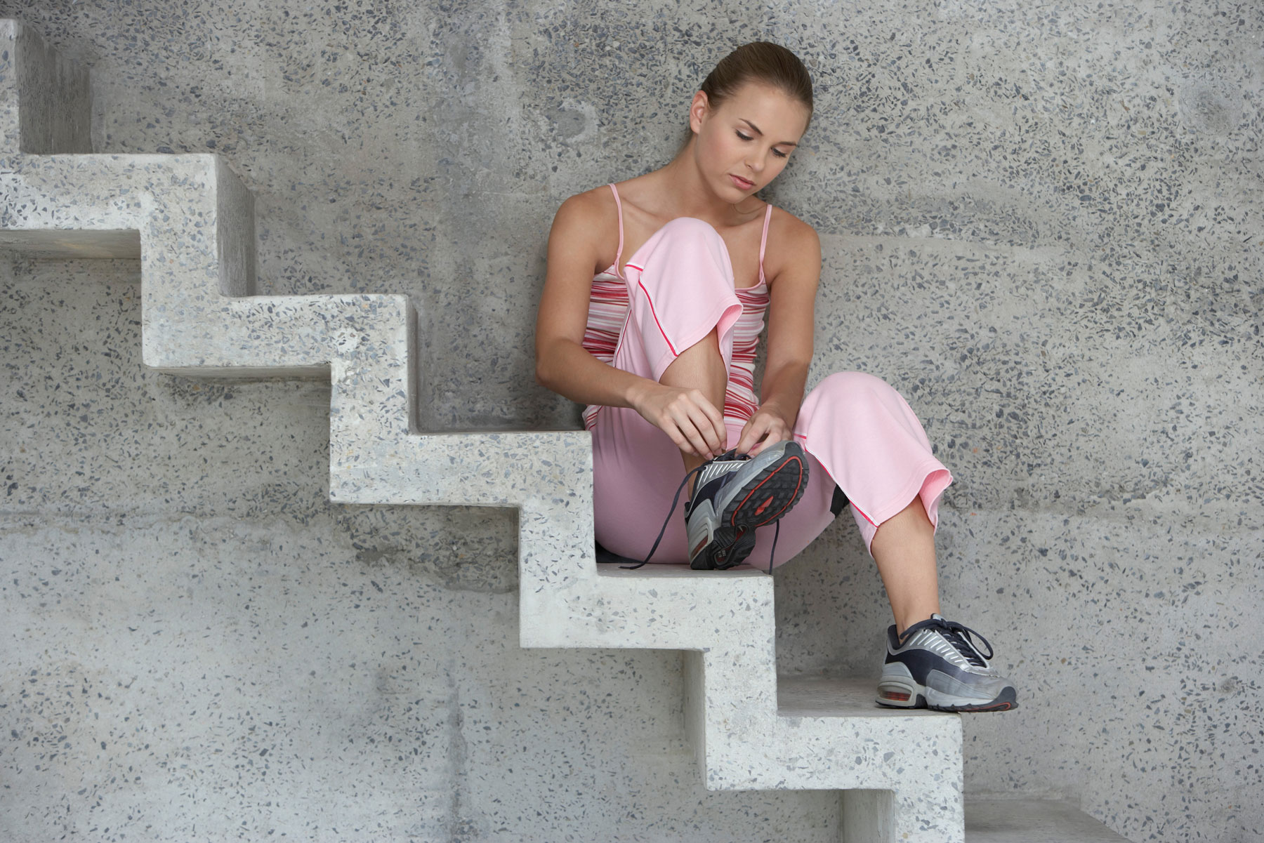 Stairs workout, stair exercises to do at home - woman resting on stairs