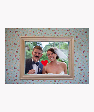 Bride and groom in wedding photobooth with props