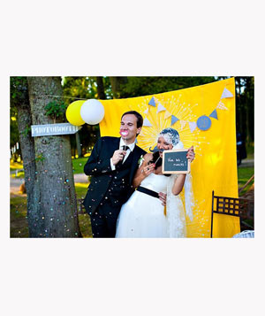 Wedding photobooth with bright yellow backdrop